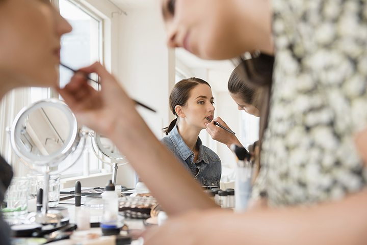 a woman having her make-up applied, shot past the make-up artist into a mirror