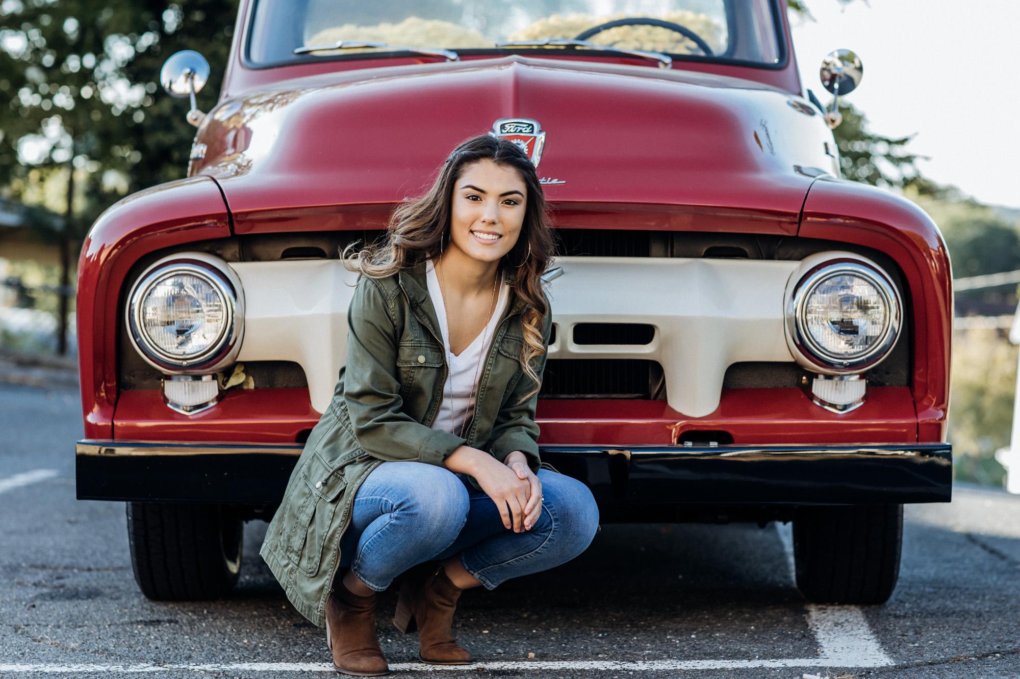 girl kneeling in front of old truck for senior portraits in warrantor Virginia
